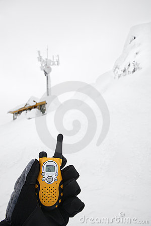 Hand holding walkie talkie in snow.