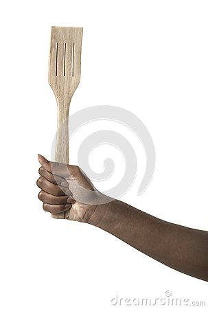 Hand holding a wooden spatula