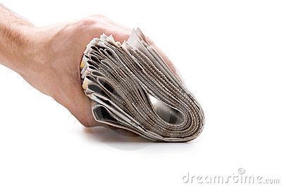 Hand holds a bundle of newspapers