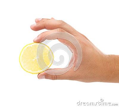 Hand holds lemon slice.