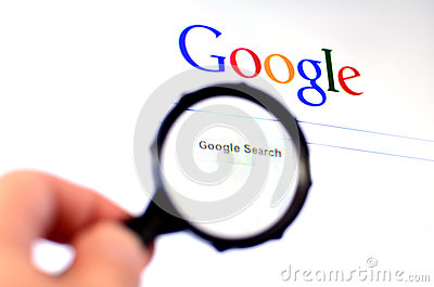 Hand holds Magnifying glass against Google homepage Editorial Image