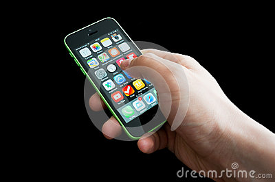 Hand with the home screen of an iphone 5C Editorial Stock Image