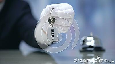 Hand im Handschuh, der Hotelzimmerschlüssel hält, überprüfen herein an der Aufnahme, Mietwohnung stock footage