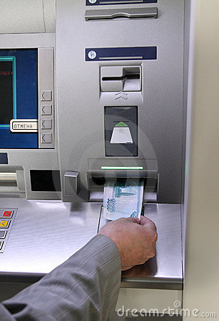 Hand inserting banknote into cash dispense