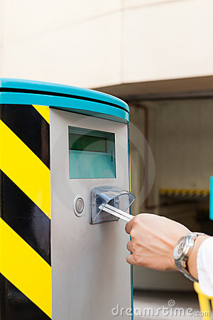 Hand is inserting parking ticket into barrier of g