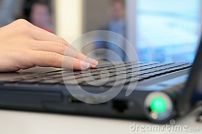 Hand on the laptop keyboard.