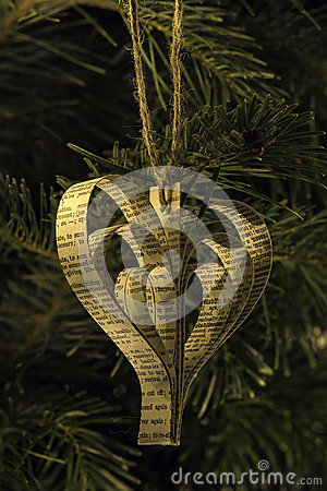Hand made paper heart shape christmas toy on the tree