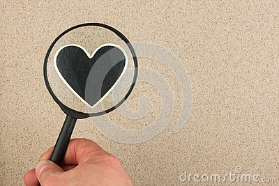 Hand with magnifying glass over the heart in the sand