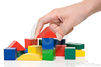 hand make a building of colored blocks.
