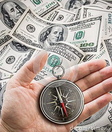 Hand met kompas meer dan honderd dollars. Financiënconcept.