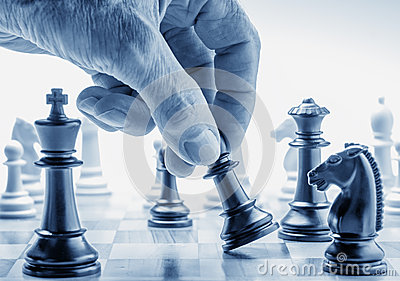 Hand moving a chess piece on board
