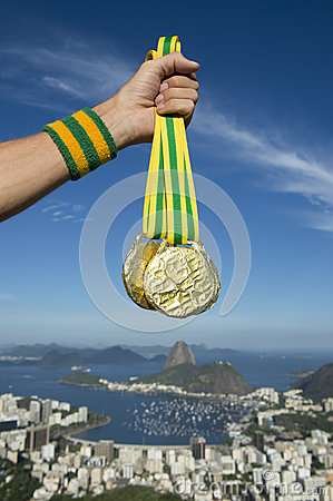 Free Hand Of Olympic Athlete Holding Gold Medals Rio Skyline Stock Photo - 53363490