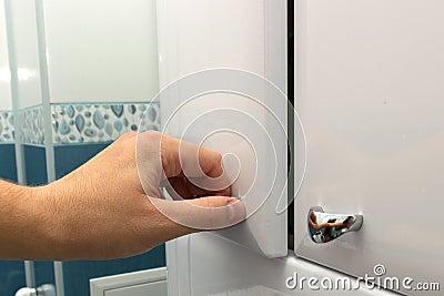 Hand opening a cabinet door