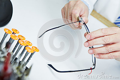 Hand of optician fixing glasses