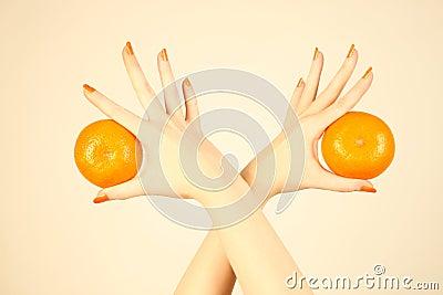 Hand with orange tangerine.