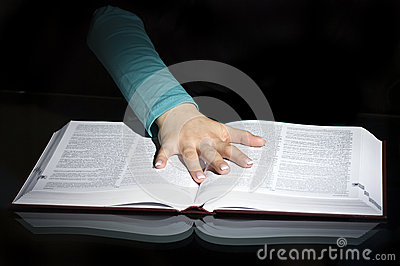Hand on pages of open book