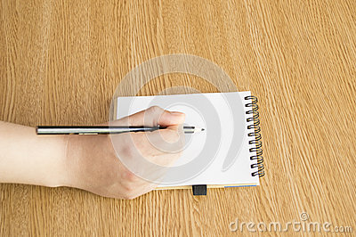 Hand with pen writing down notes