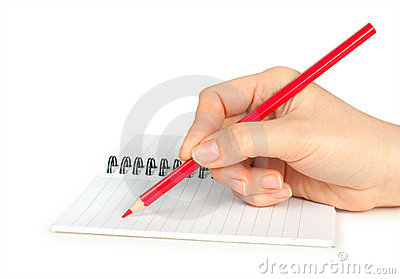 Hand with pencil writing on notebook