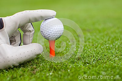 Hand placing golf-ball on tee over beautiful golf