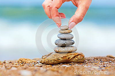 Hand placng the last pebble of a stacked tower