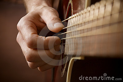 Hand playing acoustic guitar