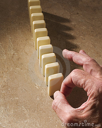 Hand poised to knock down dominoes