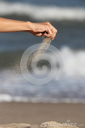 hand pours the sand