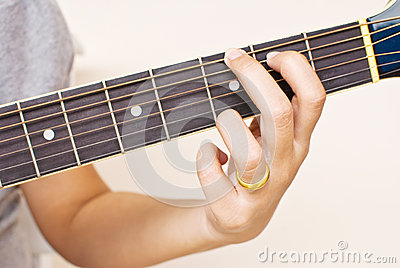 Hand pressing classic acoustic guitar chord.