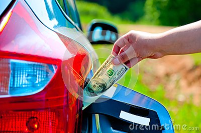 Hand puts the car into the gas tank one hundred dollars