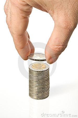 An hand puts a coin over a pile of money