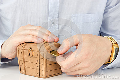 Hand putting coin into a money-box