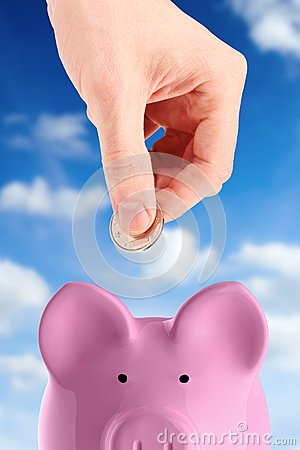 Hand putting a coin into piggy bank