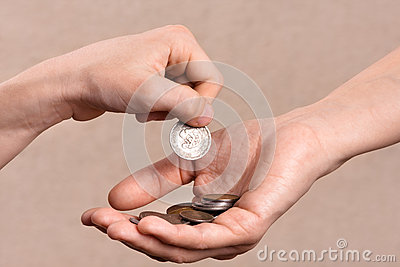Hand putting coins in the palm of another person, closeup