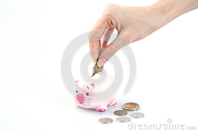 Hand putting money in a piggy bank