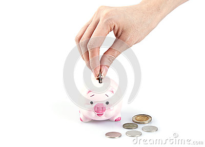 Hand putting money in a piggy bank