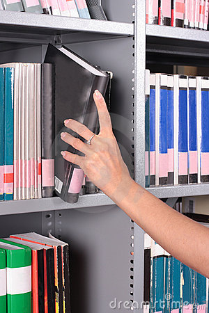Hand reaching for book on a shelf