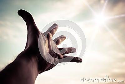 Hand reaching to towards sky.