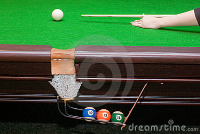 Hand ready to hit a white ball with cue