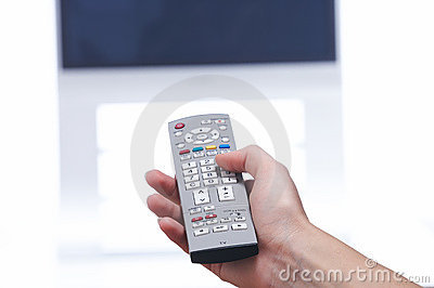 Hand with remote control and tv set