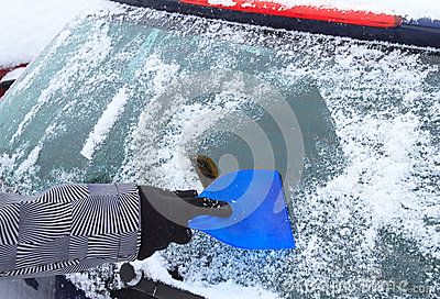 Hand scraping ice from the car window