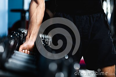 Hand selecting a dumbbell