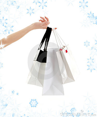 Hand with shopping bags and snowflakes