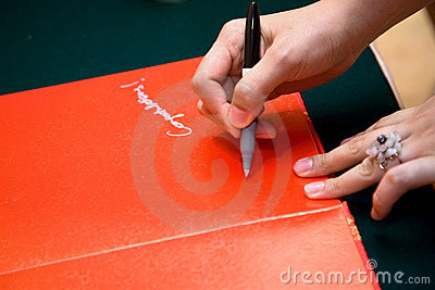 Hand signing on a red guests book
