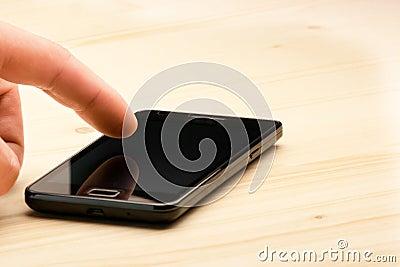 Hand touching screen of black smartphone