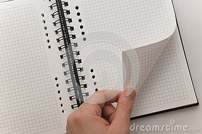 Hand turning page of blank spiral notebook