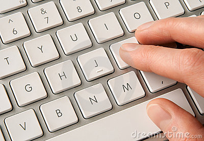 Hand typing on white computer keyboard