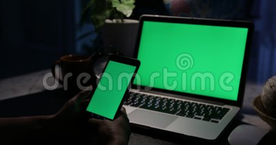 Hand using smartphone and a laptop computer with green screen . Dolly in. Hand is using smartphone and a laptop computer with green screen . Dolly in stock video