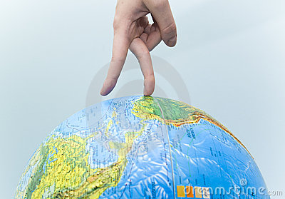 A Hand Walking Around a Globe.