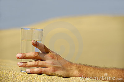 Hand with water in desert