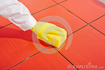 Hand with yellow gloves and sponge clean tiles